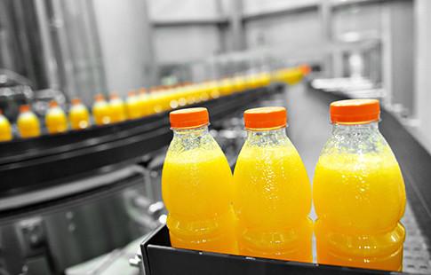 orange juice bottles on filling machine conveyor belt